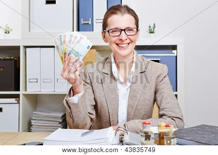Smiling senior business woman in office with Euro money banknotes