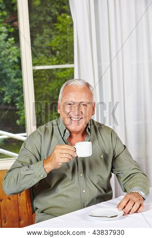 Happy retired man drinking a cup of coffee in a rest home