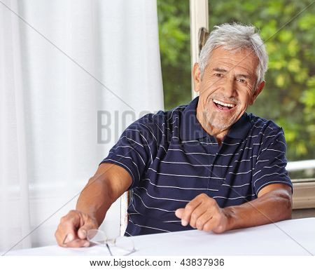 Happy smiling senior man sitting with reading glasses at a table