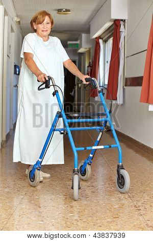 Senior woman walking with walker though a hospital