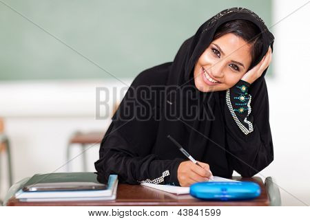 happy female middle eastern high school student sitting in classroom