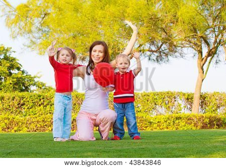 Mother with two cute kids raising hands up and enjoying sunny day, happy young family waving hand in spring park, woman with daughter and son having fun outdoors, happiness concept
