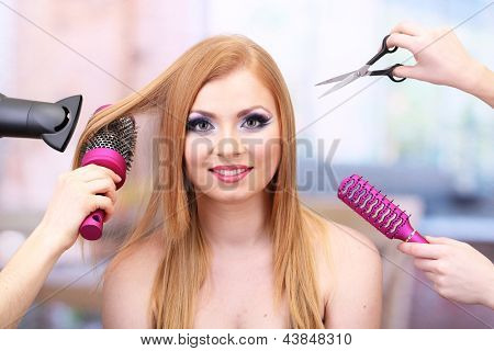 Beautiful woman and hands with brushes, scissors and hairdryer in beauty salon