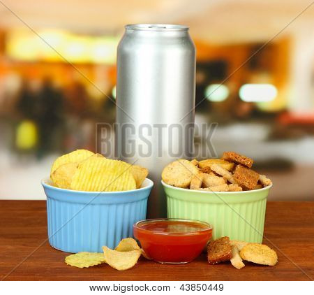 Snacks and beverage in metal can, on bright background