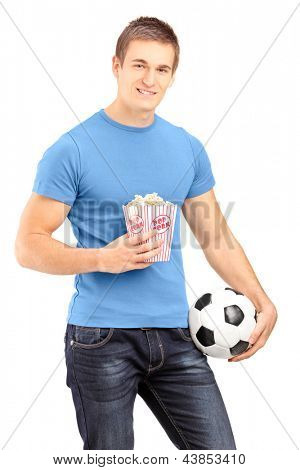 Male sports fan holding a football and popcorn box isolated on white background