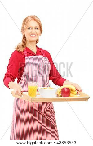 A smiling mature woman in apron carrying a tray with drinks and food isolated against white background