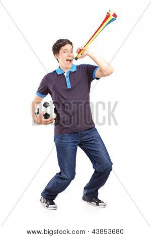 Full length portrait of a male sport fan holding a football and horn isolated on white background