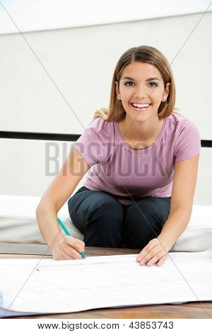 Portrait of pretty young female architect smiling while drafting blueprint