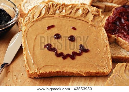 Making peanut butter sandwiches with personality!  Fun smiley face drawn on with jam. Creamy peanut butter with jam on whole grain wheat bread on wood cutting board. Macro with shallow dof.