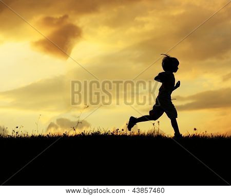 Boy running on the meadow at sunset