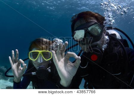 Scuba divers underwater showing ok signal