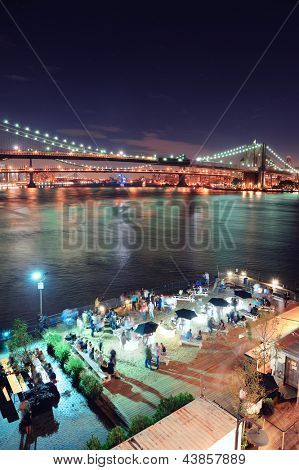 Brooklyn Bridge over East River at night in New York City Manhattan with lights and reflections and people in club bar enjoying the view.
