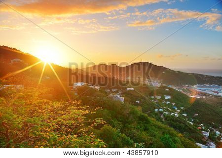 Virgin Islands St Thomas sunrise with colorful cloud, buildings and beach coastline.