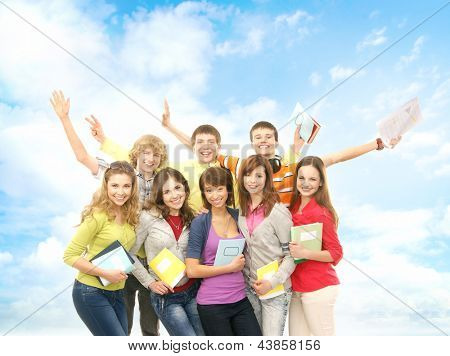 Group of smiling teenagers staying together and looking at camera over the summer background