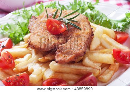Viener schnitzel, breaded steak with french fries and cherry tomato