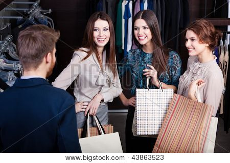 Girls consult with shop assistant of the store