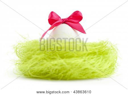Egg with pink bow is in the nest of sisal filler, isolated on white