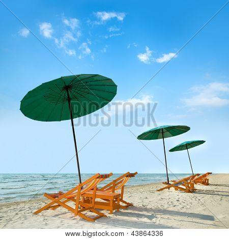 Beach chairs and umbrella on tropical sand beach.