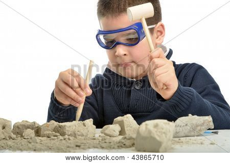 Child using tools at an archeology dig site