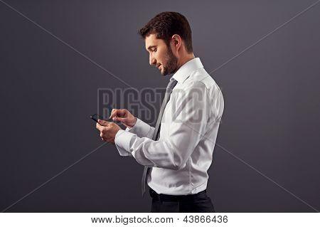 Retrato de la vista lateral del empresario con tablet pc. Studio disparó sobre el fondo oscuro