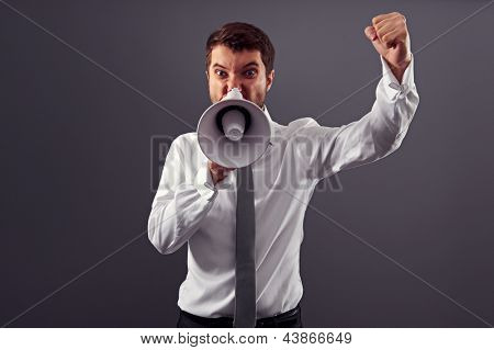 angry businessman clenching his fist and shouting in megaphone