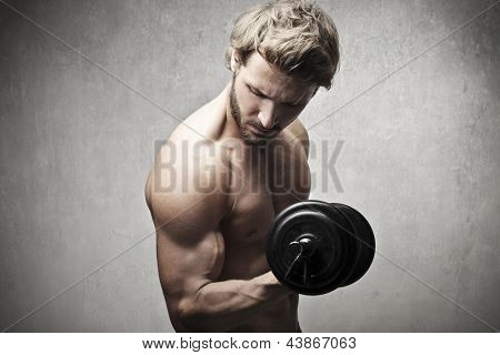 muscular man raises dumbbell
