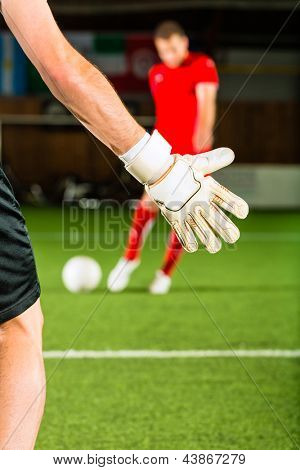 Man scoring a goal at indoor football or indoor soccer