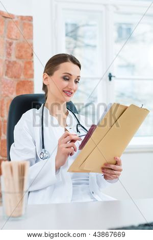 Young female doctor sitting at a desk in front of window in clinic reading a file or dossier