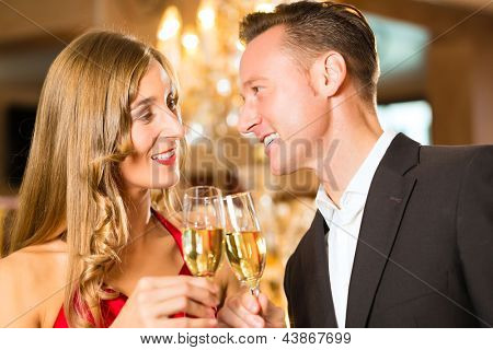Couple, man and woman, drinking champagne in a fine dining restaurant, each with glass of sparkling wine in hand