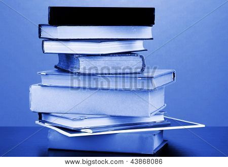 Stack of interesting books and magazines on wooden table on orange background