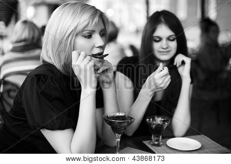 Two young women eating a dessert at sidewalk cafe