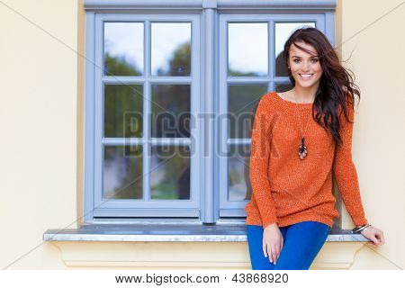 Beautiful young woman sitting in a window