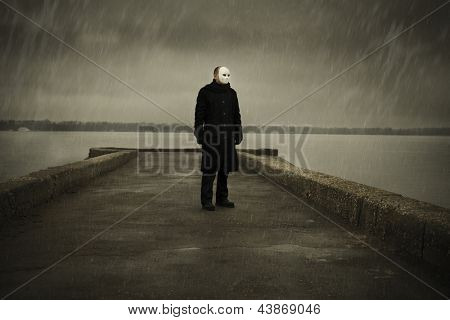 man with white mask near the river and rainy day