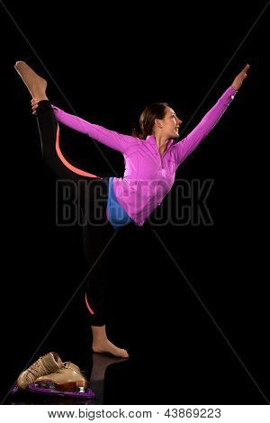Figure skater stretching. Studio shot over black.