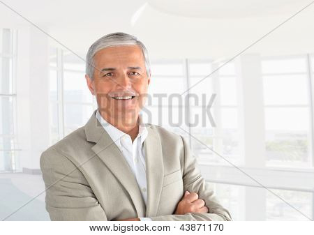 Closeup of a casual businessman in a modern office with his arms folded. Horizontal Format.