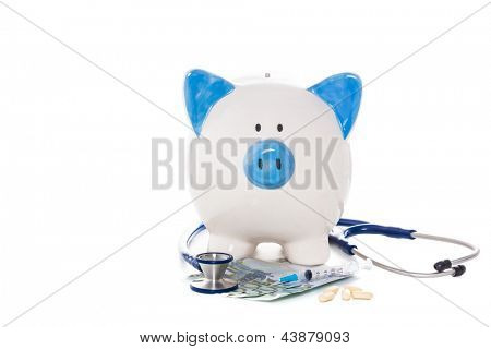 Blue and white piggy bank sitting on euro notes with stethoscope syringe and pills