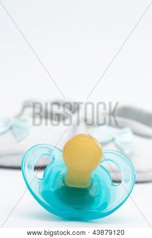 Chupeta azul na frente de botinhas de bebé em fundo branco