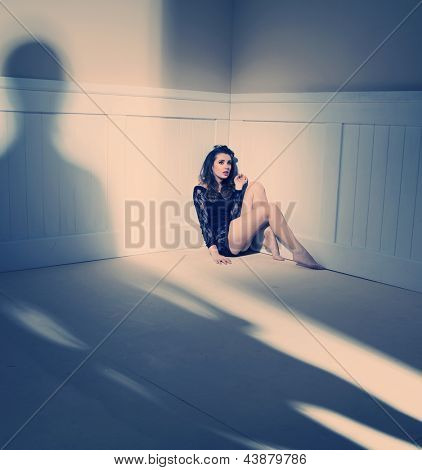 sad woman sitting alone in a empty room
