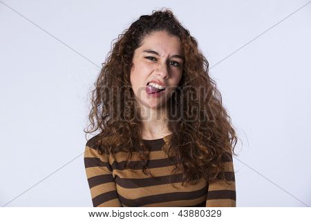 Upset young woman with her tongue out showing the piercing