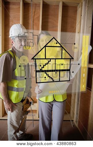 Architect and foreman standing behind house plan interface hologram