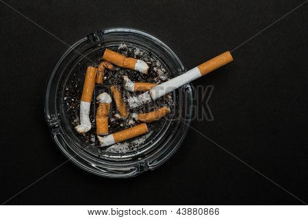 Burning cigarette left in ashtray on black background