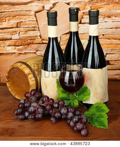 Composition of wine, wooden barrel and  grape, on stone background