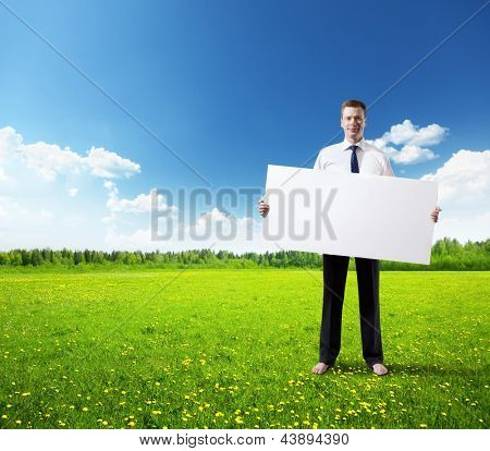 business man with empty board in hand on field of spring grass