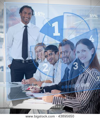 Smiling business people using blue pie chart interface in a meeting