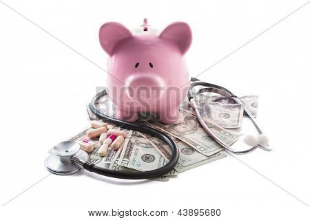 Piggy bank tablets stethoscope resting on pile of dollars on white background