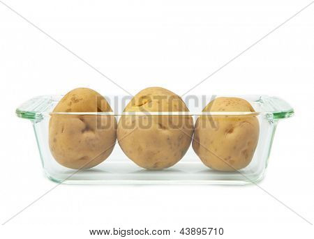 Preparing potatoes for cooking. Three potatoes in a heat resistant glass oven dish, isolated on white.