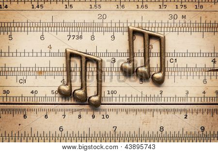 Musical timing, rhythm. beat and groove, concept image. Brass notes on a vintage calculation rule.