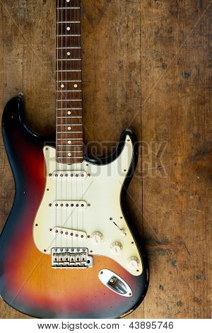 Sunburst color guitar with very old wood surface in background.