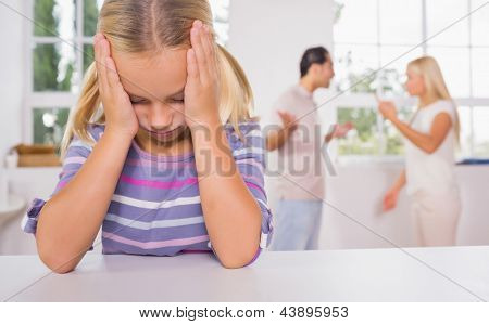 Little girl looking depressed in front of fighting parents in the kitchen