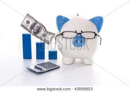 Blue and white piggy bank wearing glasses with blue graph model and calculator on white background